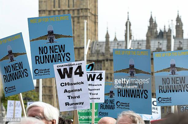 Protesters hold signs during a rally against a third runway at Heathrow airport in Parliament Square on October 10 2015 in London England Before...