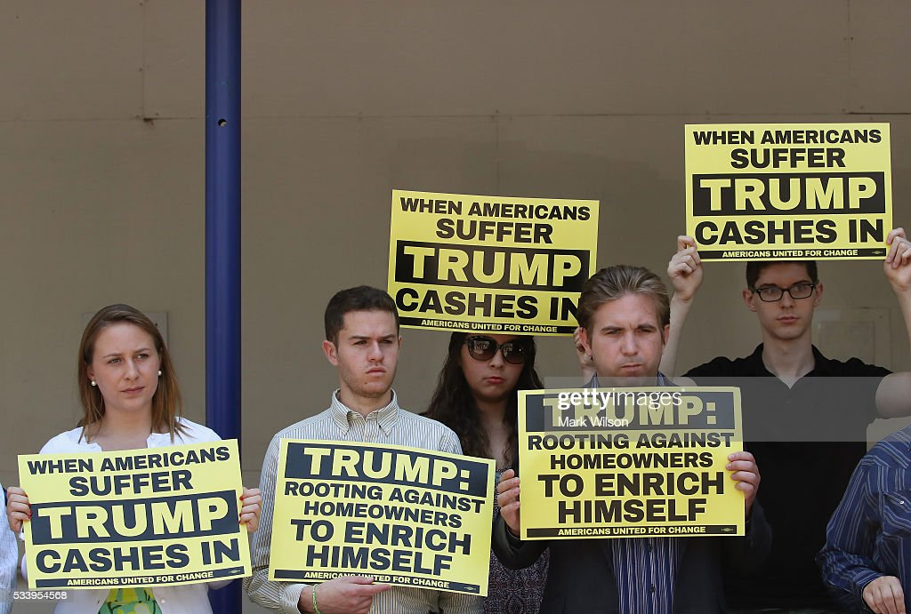Protesters hold signs in front of Donald Trumps new Trump International Hotel to demand that he release his tax returns, May 24, 2016 in Washington, DC. Protesters with the group Americans United For Change, challenged Trump to release his returns and reveal how much he profited off Americans misfortune during the housing crisis.
