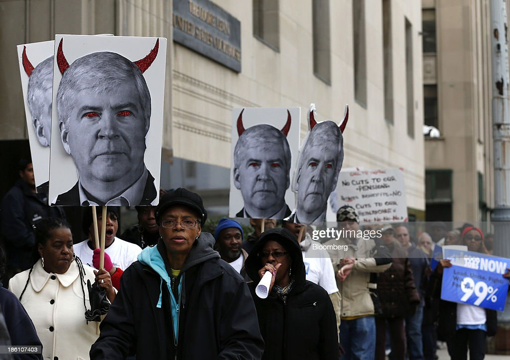 Protesters hold signs of Michigan Governor Rick Snyder during a demonstration outside of the Theodore Levin United States Courthouse in Detroit, Michigan, U.S., on Monday Oct. 28, 2013. Snyder told a federal judge that he considers Detroits bankruptcy the 'largest issue' facing the U.S. Photographer: Jeff Kowalsky/Bloomberg via Getty Images