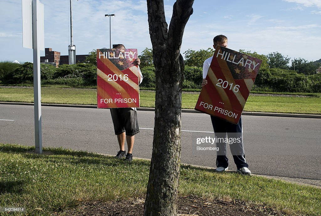 Protesters hold signs outside of a campaign event with Hillary Clinton, former Secretary of State and presumptive Democratic presidential nominee, not pictured, in Cincinnati, Ohio, U.S., on Monday, June 27, 2016. Clinton released a new national television ad on Sunday attacking likely Republican rival Donald Trump for his comments on the U.K's decision to leave the European Union, and later warned of the negative impact that 'bombastic' behavior can have at times of crisis. Photographer: Ty Wright/Bloomberg via Getty Images