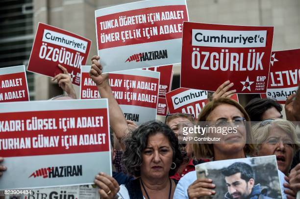 Protesters hold signs reading 'Freedom to Cumhuriyet' during a demonstration against the arrest of the newspaper's journalists outside the courthouse...