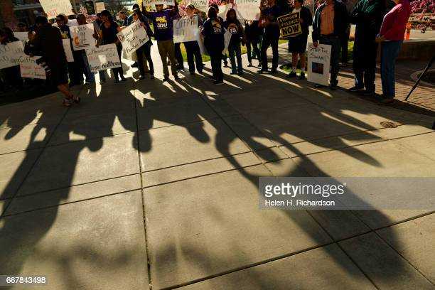 Protesters hold signs shwoing their disapproval of USs Representative Mike Coffman outside of the Education Building South 2 on the CU Anschutz...