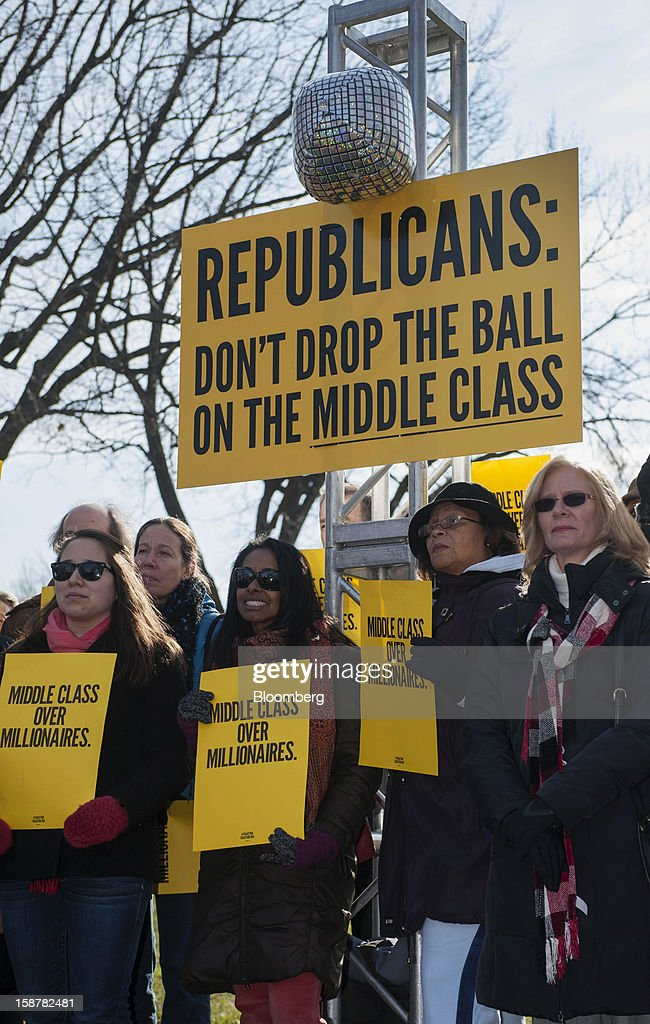 Protesters hold signs that read, 'Middle Class Over Millionaires' while standing under a sign that reads, 'Republicans: Don't Drop the Ball on the Middle Class' on the grounds of the U.S. Capitol in Washington, D.C., U.S., on Friday, Dec. 28, 2012. President Barack Obama is set to propose a scaled-back package at a meeting with congressional leaders to avert tax and spending changes that could trigger a recession in 2013, a Democratic aide with knowledge of the talks said. Photographer: Jay Mallin/Bloomberg via Getty Images