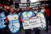 Protesters hold signs while standing a few blocks away from the World Trade Organization November 29 1999 After a three hour delay DirectorGeneral...