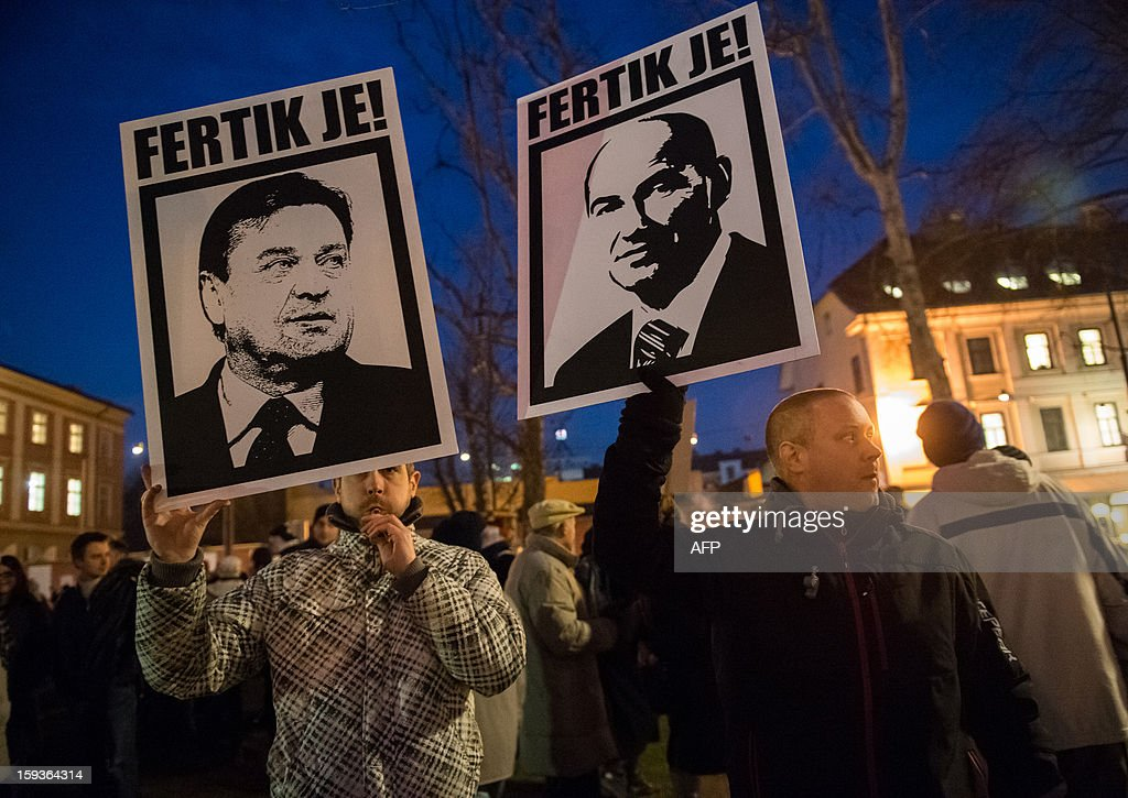 Protesters hold signs with images of Slovenian Prime Minister Janez Jansa and the mayor of Ljubljana Zoran Jakovic and reading 'You are done !' during a demonstration against political corruption and the Prime Minister in Ljubljana, on January 11, 2013. Several thousand people in Slovenia's capital today joined in one of the biggest anti-government rallies in recent months, demanding the resignation of Prime Minister Janez Jansa, who has been accused of corruption. State radio estimated over 10,000 people took part in the protest called by civil groups under the slogan 'For the government's resignation and the renewal of Slovenia.' Police put the figure closer to 8,000. AFP PHOTO / Jure Makovec
