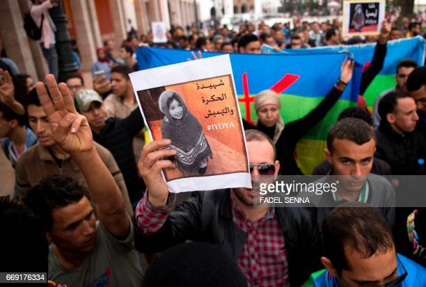 Protesters hold the Amazigh flag and pictures of Idya Fakhreddine as they shout slogans in Rabat on april 16 following the death this twoyearold...