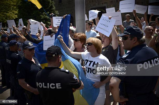 Protesters hold Ukrainian flags signs reading 'Putin Killer' as they shout slogans in front of the Bulgarian Presidency as Bulgaria's president meets...