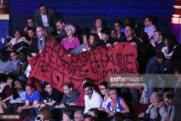 Protesters hold up a banner at the Cirque d'Hiver in Paris on September 8 during a meeting by the Socialist Party entitled 'L'accueil des réfugiés...