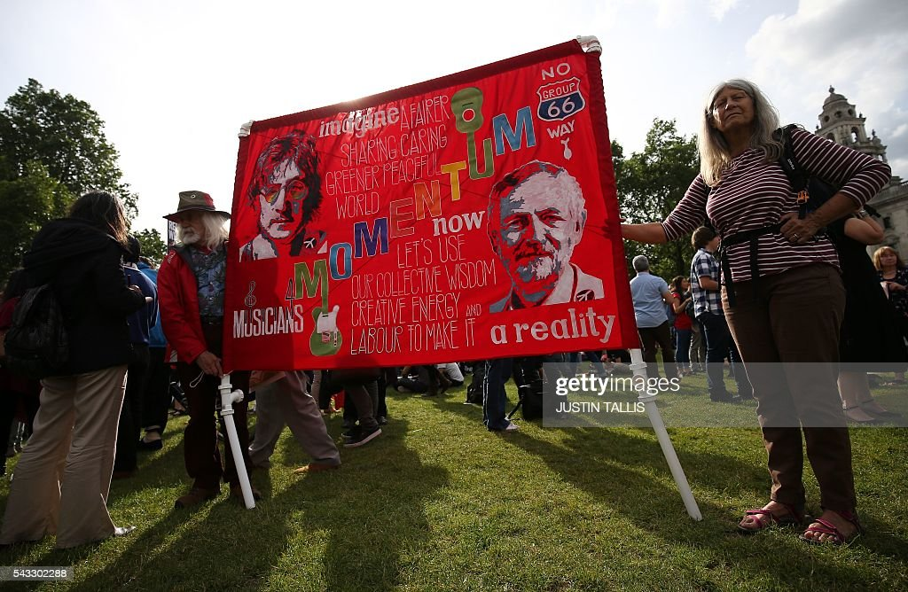 Protesters hold up a banner in support of Leader of the opposition Labour Party Jeremy Corbyn is pictured on a flagpole outside parliament during a pro-Corbyn demonstration in central London on June 27, 2016. Britain's historic decision to leave the 28-nation bloc has sent shockwaves through the political and economic fabric of the nation. It has also fuelled fears of a break-up of the United Kingdom with Scotland eyeing a new independence poll, and created turmoil in the opposition Labour party where leader Jeremy Corbyn is battling an all-out revolt. TALLIS