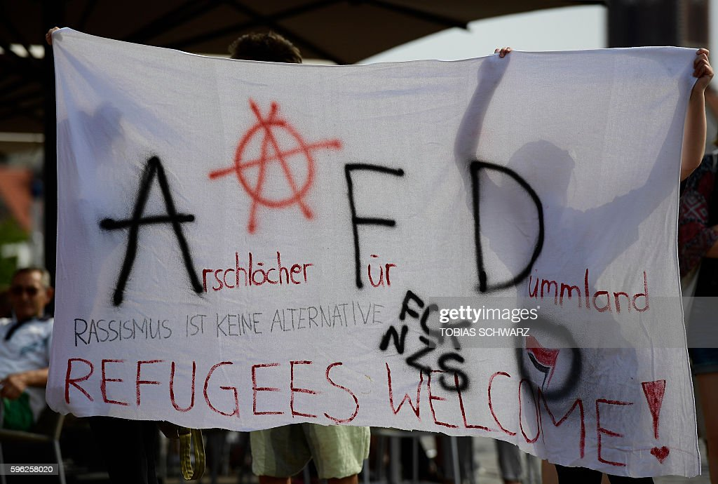 Protesters hold up a banner reading 'Arschloecher fuer Dummland' 'Racism is no Alternative' during an election rally of the Alternative for Germany...