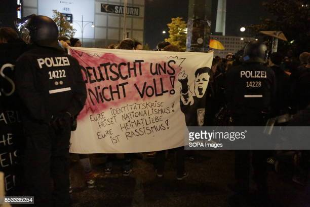 Protesters hold up a banner that reads 'Don't German us Your identity crisis fuels nationalism Your love for your homeland is racism' Police officers...