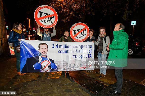 Protesters hold up a placard reading '34 million Europeans count on Wallonia stop CETA' as a meeting on CETA takes place at the Walloon parliament in...
