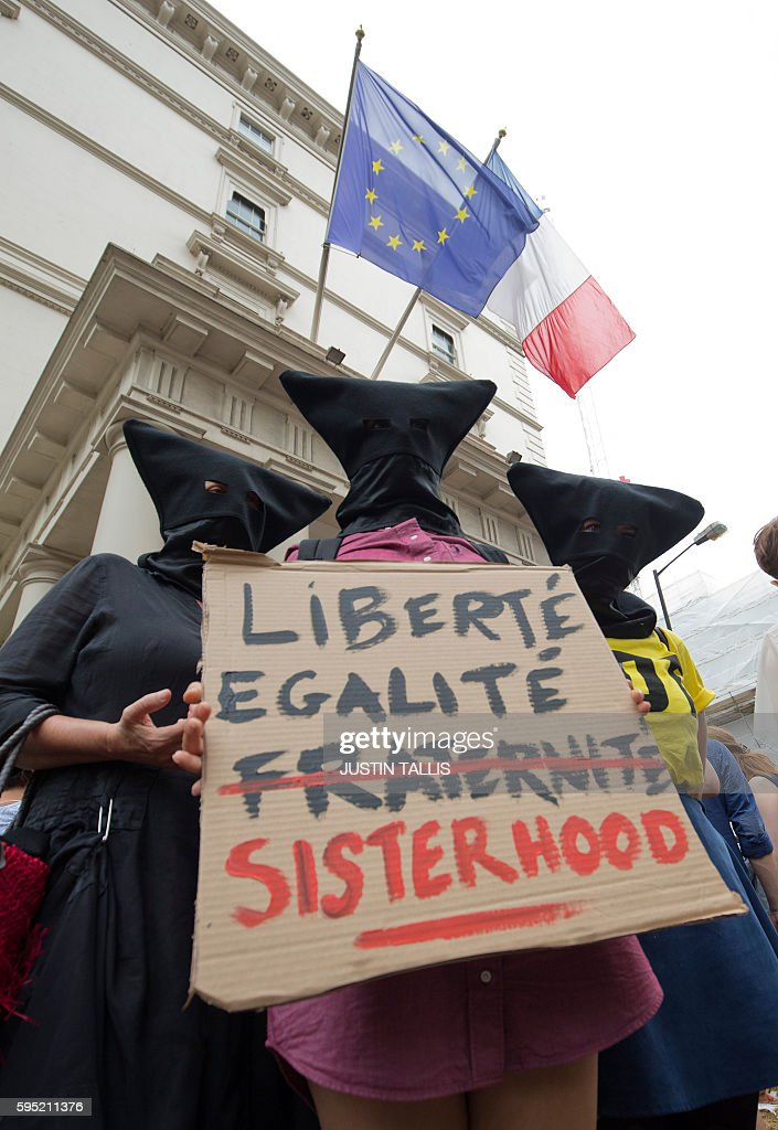 Protesters hold up a placard with a modified version of the French national motto outside the French Embassy in London on August 25 during a 'Wear...