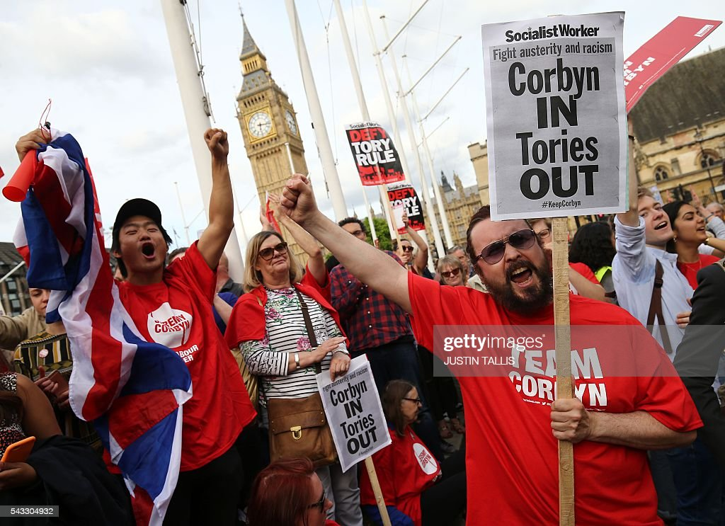 Protesters hold up a placards in support of Leader of the opposition Labour Party Jeremy Corbyn outside parliament during a pro-Corbyn demonstration in central London on June 27, 2016. Britain's historic decision to leave the 28-nation bloc has sent shockwaves through the political and economic fabric of the nation. It has also fuelled fears of a break-up of the United Kingdom with Scotland eyeing a new independence poll, and created turmoil in the opposition Labour party where leader Jeremy Corbyn is battling an all-out revolt. TALLIS