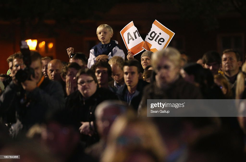 Protesters hold up a torn 'Angie' sign, in refernce to German Chancellor and Chairwoman of the German Christian Democrats (CDU) Angela Merkel, on the edge of a CDU election rally at which Merkel spoke on September 16, 2013 in Potsdam, Germany. Germany faces federal elections on September 22 and so far the CDU has a strong lead in polls over the opposition.