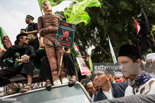Protesters hold up an effigy of Myanmar monk Wirathu as thousands of members of various Indonesian muslim groups demonstrate in support of Myanmar's...