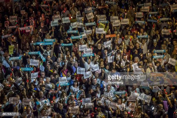 Protesters hold up banners during a candlelit vigil to demand the release of imprisoned seperatist leaders Jordi Sanchez head of the Catalan National...