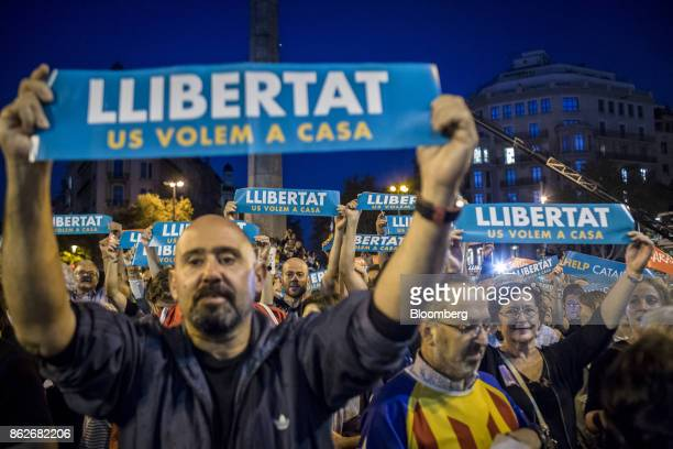 Protesters hold up banners reading 'Help Catalonia' during a candlelit vigil to demand the release of imprisoned seperatist leaders Jordi Sanchez...