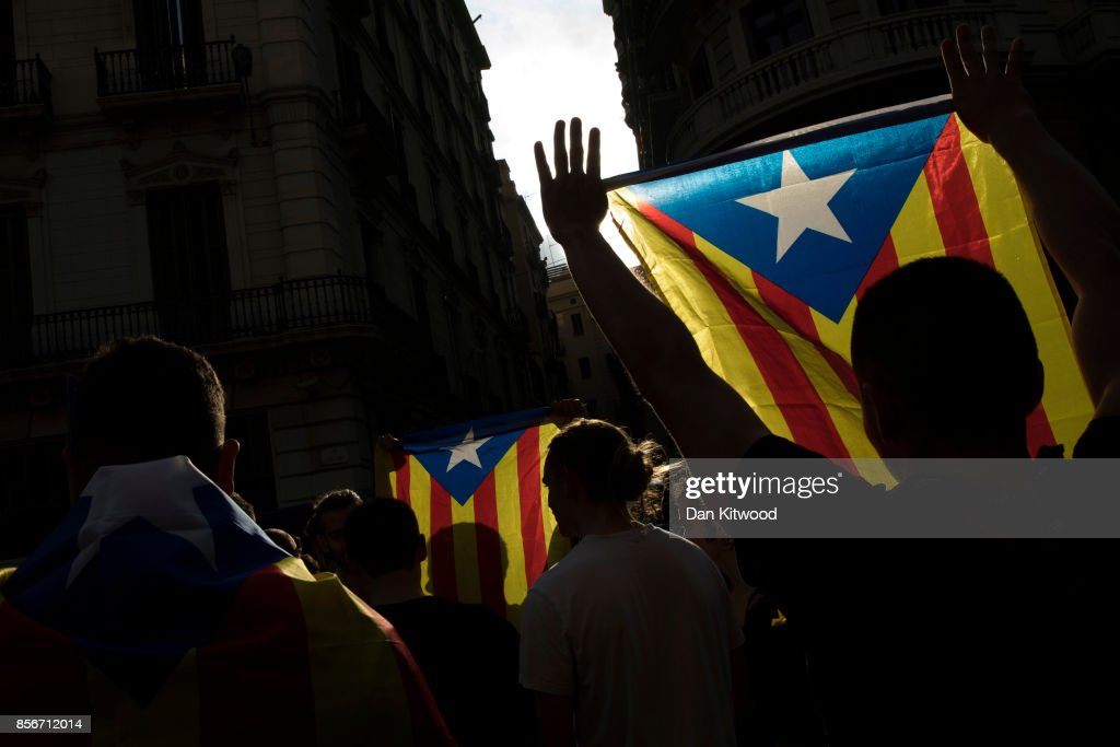 Protesters hold up flags as they gather outside the 'General Direction of the National Police of Spain', offices as Catalonian police officers surround the building on October 2, 2017 in Barcelona, Spain. Catalonia's government met Monday to discuss plans to declare independence after the results of yesterday's disputed referendum.