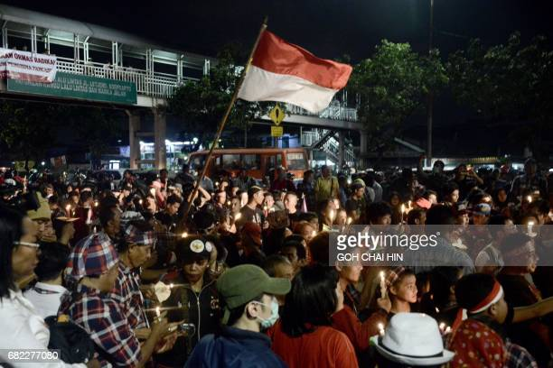 Protesters hold up lighted candles and flags as they protest outside the Indonesian High Court building in Jakarta on May 12 to demand the release of...