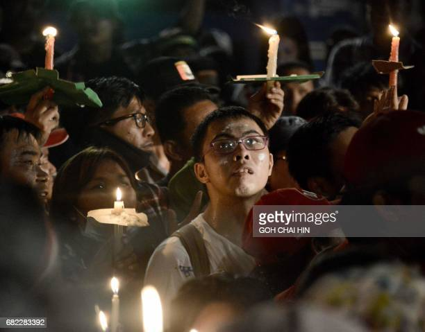Protesters hold up lighted candles during a gathering outside the Indonesian High Court building in Jakarta on May 12 to demand the release of...