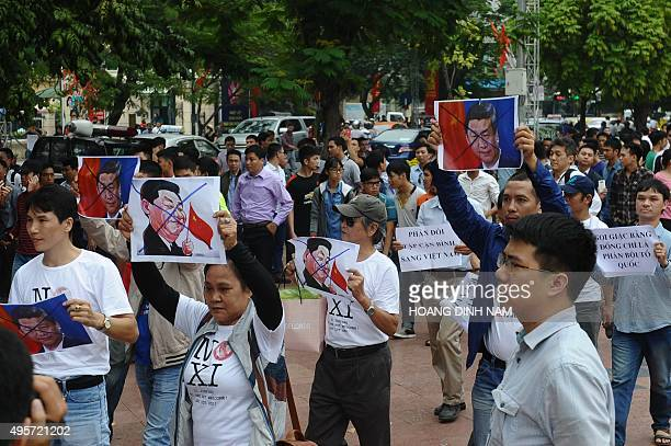 Protesters hold up marked depictions of Chinese president Xi Jinping as they march on a street leading to the Chinese embassy in downtown Hanoi on...