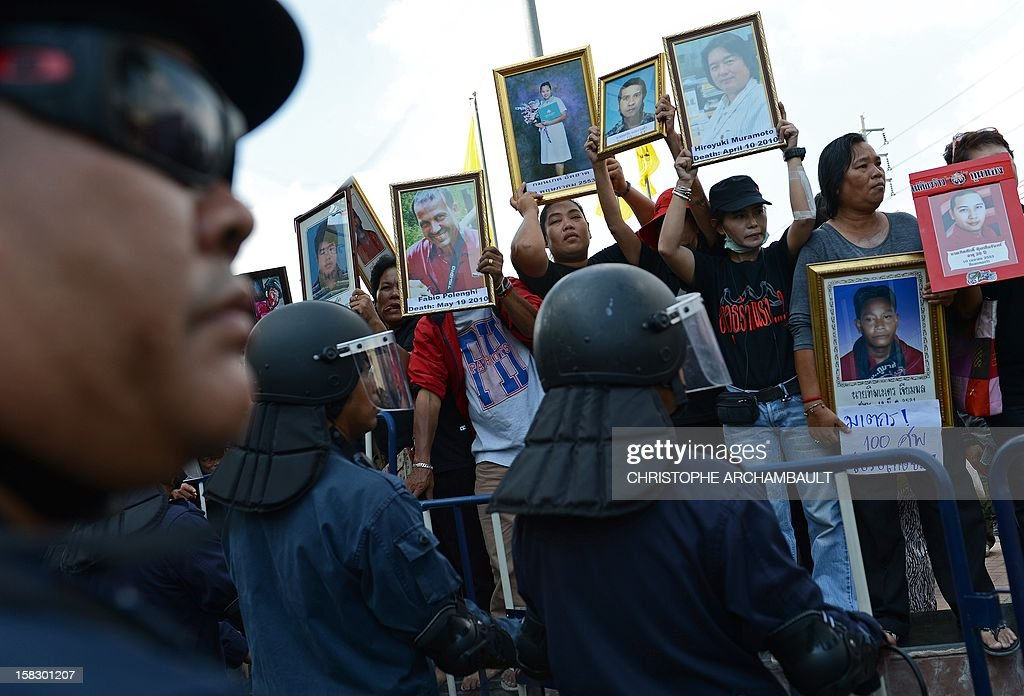 Protesters hold up pictures of some of those killed during a crackdown on anti-government rallies two years ago as former Thai prime minister Abhisit Vejjajiva (not pictured) appears at a justice ministry building to be charged with murder over a civilian's death during the crackdown in Bangkok on December 13, 2012. Abhisit, along with his then-deputy Suthep Thaugsuban, were to be charged at the Department of Special Investigation (DSI), making them the first officials to face a court over Thailand's worst political violence in decades. AFP PHOTO/Christophe ARCHAMBAULT