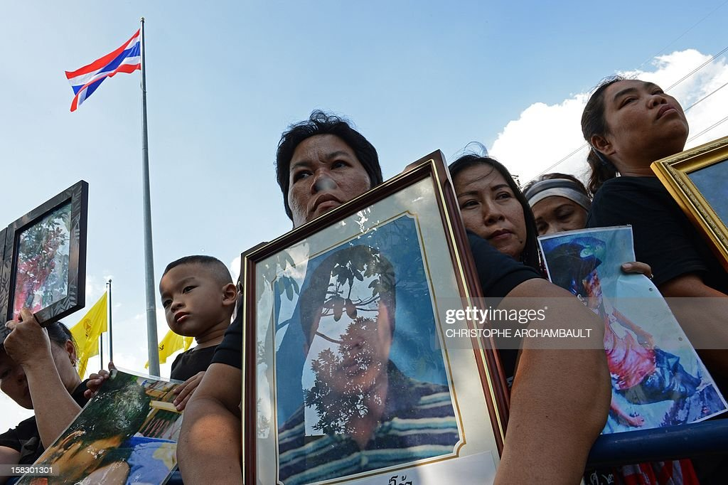Protesters hold up pictures of some of those killed during a crackdown on anti-government rallies two years ago as former Thai prime minister Abhisit Vejjajiva (not pictured) appears at a justice ministry building to be charged with murder over a civilian's death during the crackdown, in Bangkok on December 13, 2012. Abhisit, along with his then-deputy Suthep Thaugsuban, were to be charged at the Department of Special Investigation (DSI), making them the first officials to face a court over Thailand's worst political violence in decades. AFP PHOTO/Christophe ARCHAMBAULT