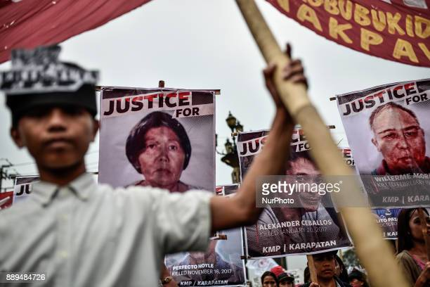 Protesters hold up pictures of victims of extrajudicial killings during Human Rights Day protests in Manila Philippines December 10 2017 On...