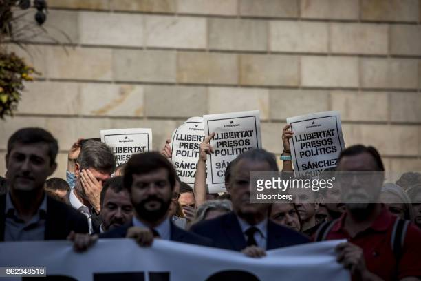 Protesters hold up posters during a silent demonstration outside the Generalitat in support of Catalan independence campaigners Jordi Sanchez and...