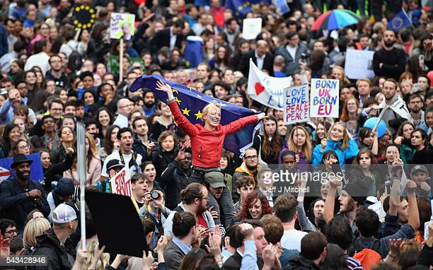 Protesters hold up signs and flags as they demonstrate against the EU referendum result outside the Houses of Parliament on June 28 2016 in London...