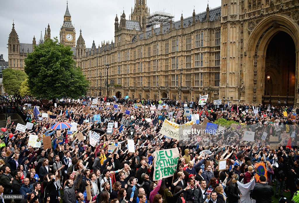Protesters hold up signs and wave in unison as they demonstrate against the EU referendum result outside the Houses of Parliament on June 28, 2016 in London, England. Up to 50,000 people were expected before the event was cancelled due to safety concerns. In the early evening a crowd still converged on the square to vent their anti-Brexit feelings, before the protest moved to the Houses of Parliament.