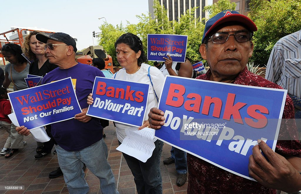 Protesters hold up signs as they demand that Wall Street banks repay what protesters claim is the 17 billion USD bailout debt that they owe the...