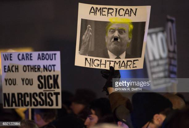 Protesters hold up signs at the 'We Stand United' rally on the eve of US Presidentelect Donald Trump's inauguration outside Trump International Hotel...