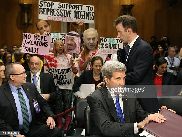 Protesters hold up signs behind Secretary of State John Kerry during a Senate Foreign Relations Committee hearing on Capitol Hill February 23 2016 in...