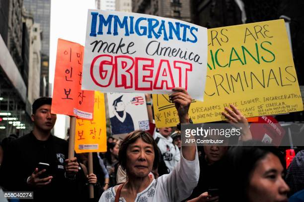 Protesters hold up signs during a demonstration against US President Donald Trump during a rally in support of the Deferred Action for Childhood...