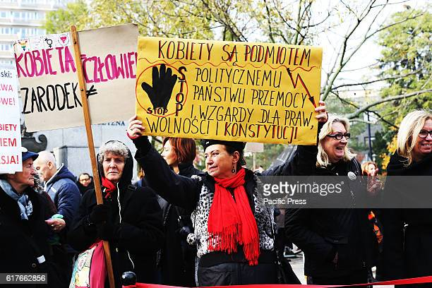 Protesters hold up signs that read ' Women are pawns in a political country where the state doesn't respect laws' during a 'black protest' in Warsaw...