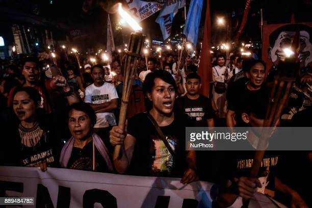 Protesters hold up torches as they shout antigovernment slogans during Human Rights Day protests in Manila Philippines December 10 2017 On...