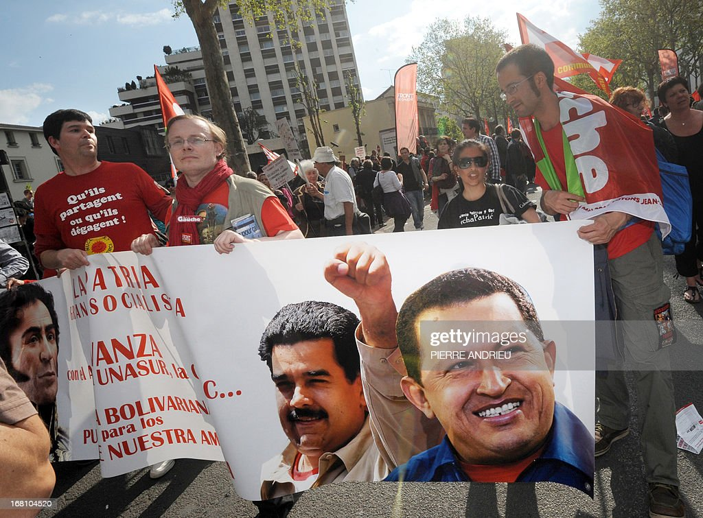 Protesters holding a banner bearing the images of late Venezuelan president Hugo Chavez (R) and incumbent Venezuelan president Nicolas Maduro (L) take part in a demonstration on May 5, 2013 in Paris, called by Jean-Luc Melenchon, leader of Front de Gauche (Left Front) left wing party, to protest 'against the austerity, against the finance and to ask for a Sixth Republic'. When France's president Francois Hollande swept to power on May 2012 on a wave of discontent, he could hardly have imagined that a year later he would be the most unpopular president in modern French history.