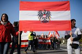 Protesters holding Austrian national flags gather during an antimigrants rally in Spielfeld Austria near the AustriaSlovenia border on October 31...