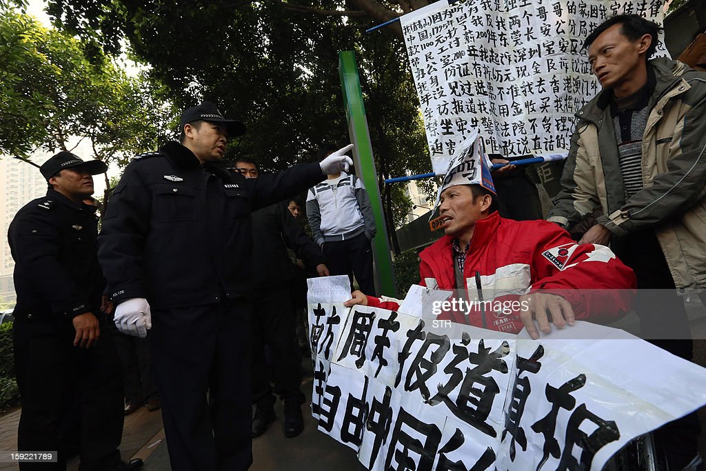 Protesters holding banners in support of greater media freedom confront police officers (L) near the headquarters of Nanfang Media in Guangzhou, on January 10, 2013. The row at the popular liberal paper, which had an article urging greater rights protection replaced with one praising the ruling communist party, has seen demonstrators mass outside its headquarters in the southern city of Guangzhou. AFP PHOTO