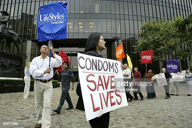 Protesters holding banners that look like giant condoms call on pornography executive Larry Flynt to voluntarily adopt a 100% condom use policy in...