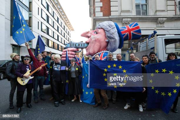Protesters holding Flags of Europe pose in front of an effigy of British Prime Minister Theresa May with a gun during a demonstration outside BBC's...