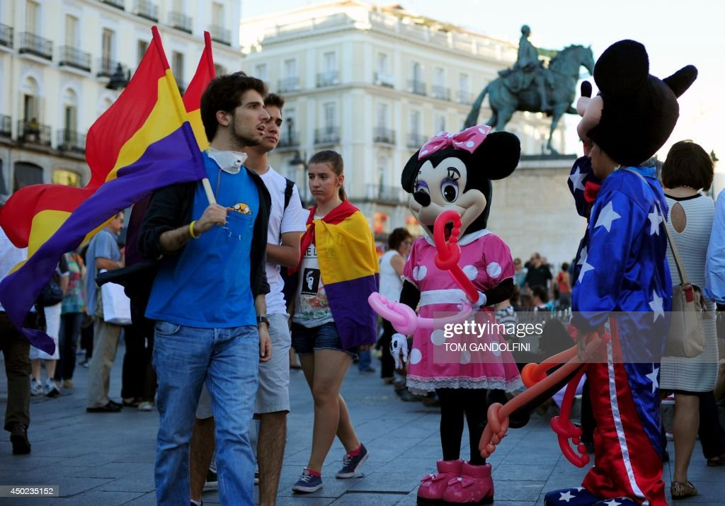 Protesters holding flags of the Spanish Second Republic walk past people dressed up as cartoon characters during a demonstration to demand a referendum on the monarchy following the abdication of King Juan Carlos, in Madrid on June 7, 2014. Dozens of left-wing political parties and citizens organisations came together to demand 'A referendum now!' on the future of the monarchy. Spanish King Juan Carlos' abdication on June 2 revived anti-royalist fervour in the young democracy, sending thousands into the streets clamouring for a referendum on the monarchy itself.