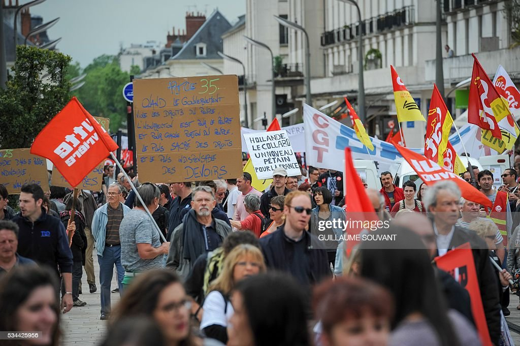 Protesters holding French CGT and Lutte ouvriere unions flags take part in a protest against the government's planned labour law reforms on May 26, 2016 in Tours, Central France. The French government's labour market proposals, which are designed to make it easier for companies to hire and fire, have sparked a series of nationwide protests and strikes over the past three months. / AFP / GUILLAUME