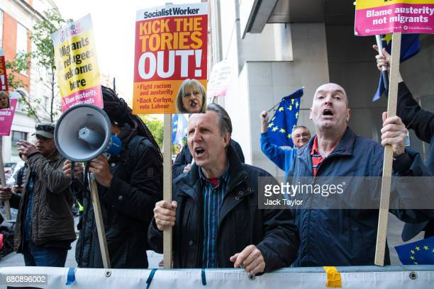 Protesters holding placards chant as they demonstrate outside BBC's Broadcasting House as British Prime Minister Theresa May and her husband Philip...