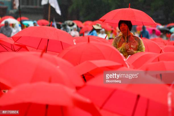 Protesters holding red umbrellas gather in front of city hall during a rally against the deployment of the Terminal HighAltitude Area Defense system...