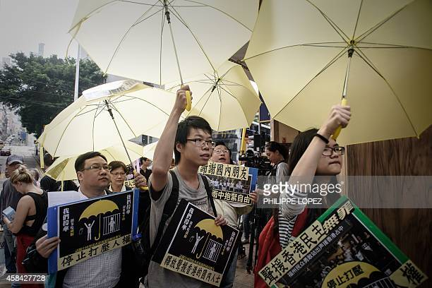 Protesters holding yellow umbrellas march towards the China liaison office in Hong Kong demanding the release of people arrested in mainland China...