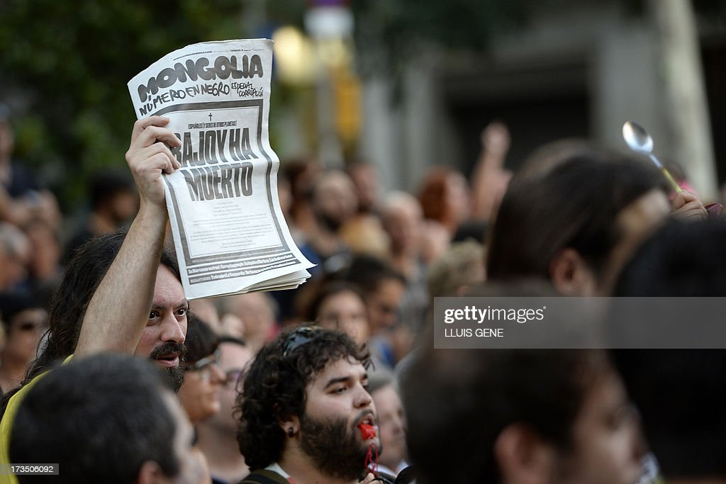 A protesters holds a copy of the newspaper 'Mongolia' reading 'Rajoy is dead' during a demonstration against corruption outside the People Party's headquarters in Barcelona on July 15, 2013. Spanish Prime Minister Mariano Rajoy faced calls today to resign or explain his ties to a slush fund scandal roiling the ruling Popular Party, whose jailed former treasurer appeared in court. The issue blew up again after the publication of friendly mobile text messages he purportedly sent to the disgraced treasurer at the heart of the affair.