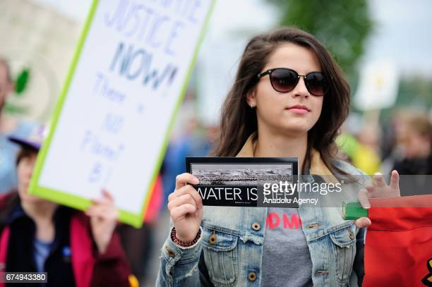 A protesters holds a 'water is life' sticker at the People's Climate March in Portland Ore United States on April 29 2017 Thousands turned out in...